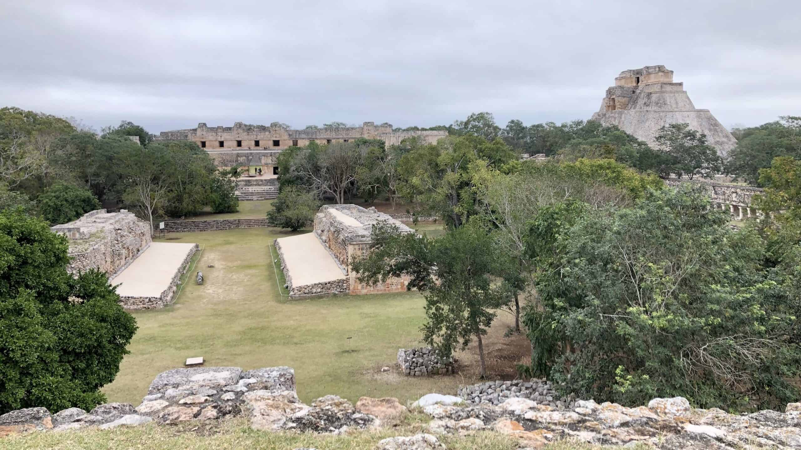 Uxmal site showing ball court and pyramid in the distance